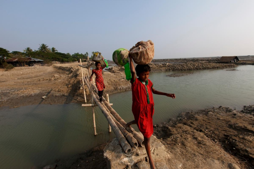 Girls cross a bamboo bridge on Katubidia island in Bangladesh, a nation where millions of people are at risk due to rising sea levels.  © UNHCR/Saiful Huq Omi