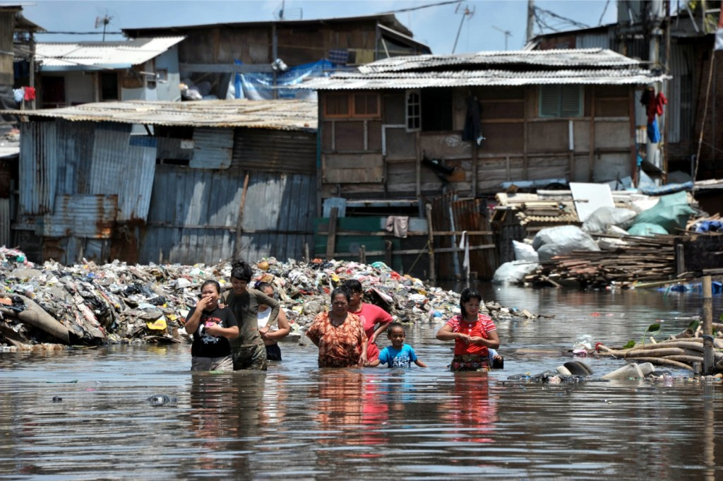 Women and children wade through their flooded Jakarta neighborhood in January, 2013. (AFP Photo)