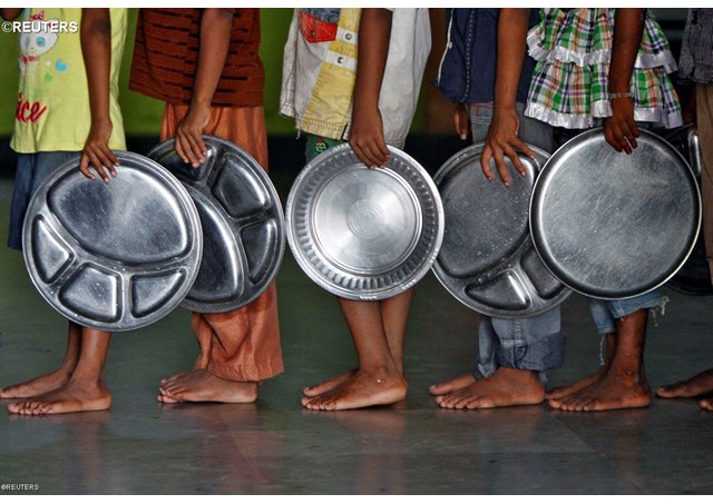 Children holding plates wait in queue to receive food at an orphanage run by an NGO in Chennai, India - REUTERS