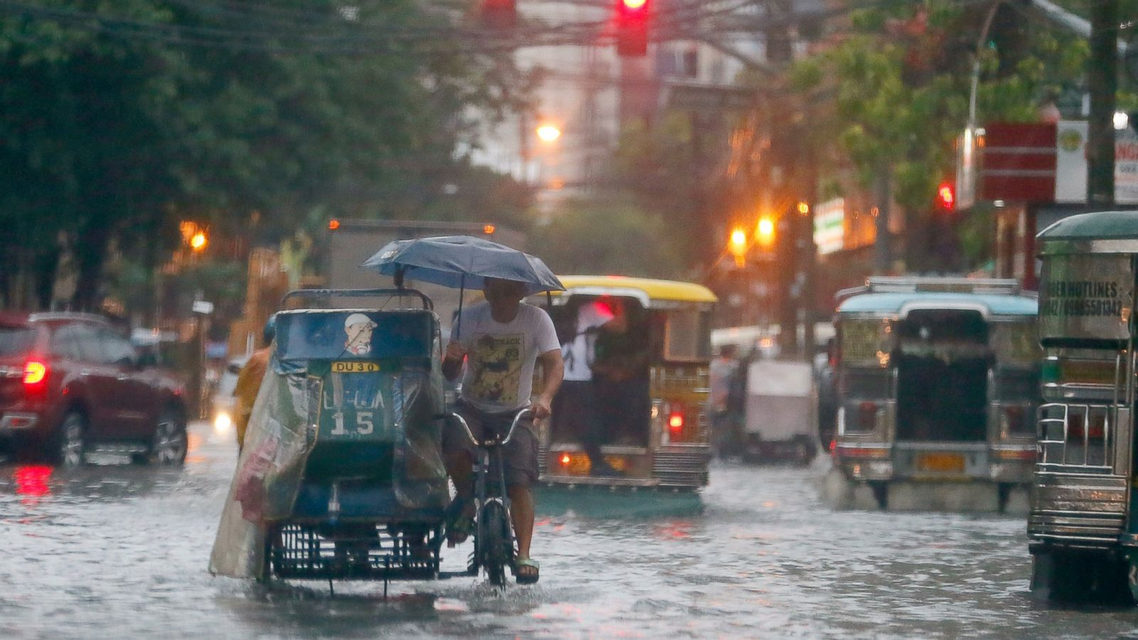 In this Aug. 26, 2016 file photo, commuters and motorists go on their way as heavy monsoon rains inundate low-lying areas in Manila, Philippines. Typhoons that slam into land in the northwestern Pacific _ especially the biggest tropical cyclones of the bunch _ have gotten considerably stronger since the 1970s, a new study concludes. (AP Photo/Bullit Marquez, File)