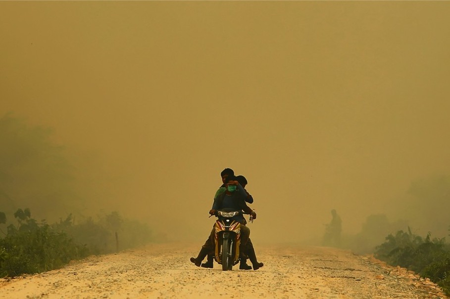 Three children persevere through haze in Dumai, Sumatra, after a series of forest fires and hotspots sent air quality to dangerous levels in June. (Reuters Photo)