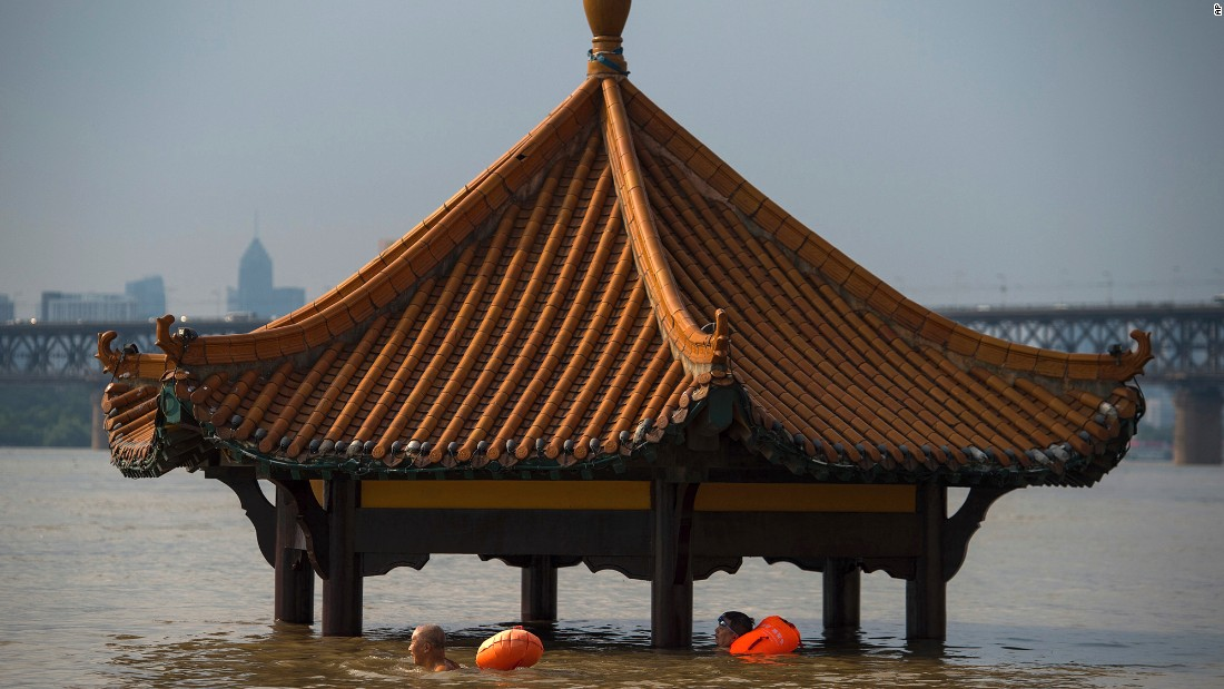 People swim past the top of a pagoda at a flooded riverside park in Wuhan on Monday, July 3.