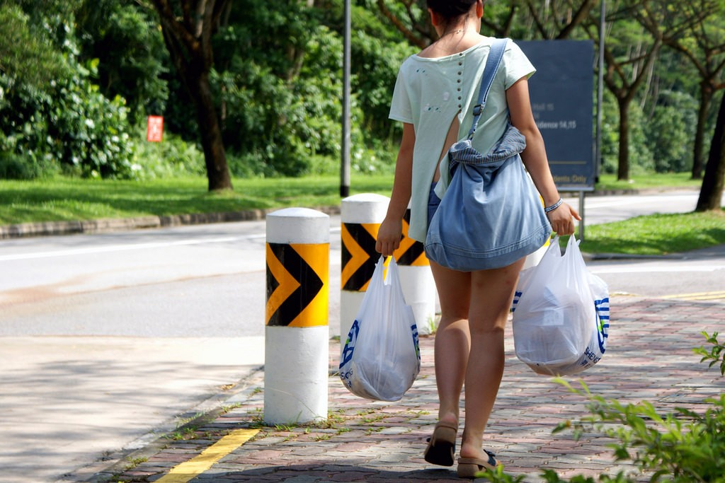 A woman carries her groceries home in plastic bags. Singapore threw away 822,000 tonnes of plastic last year, of which only seven per cent was recycled. Image: teddy-rised, CC BY-NC-ND 2.0