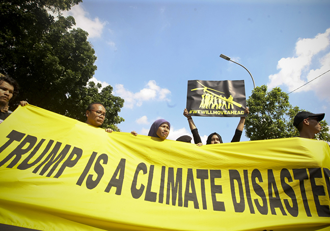 Protest banner outside the US Embassy says that Trumph is a climate disaster during protest held by Greenpeace Indonesia. Image: Yudha Baskoro/Jakarta Globe