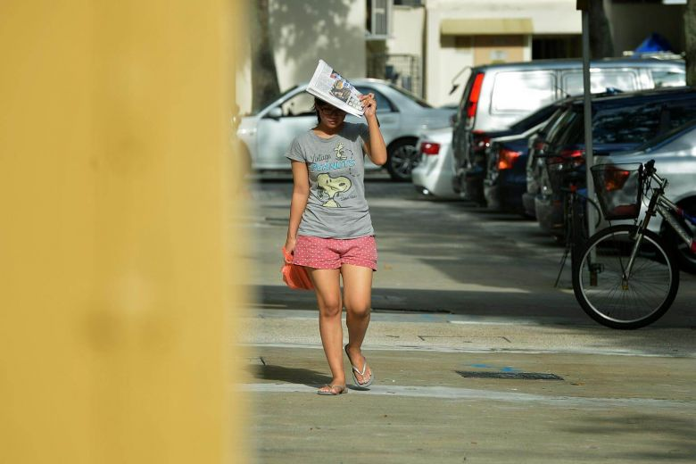 A woman using a newspaper to shade herself from the morning sun and sweltering heat at Yishun. PHOTO: ST FILE