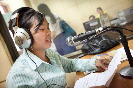 A radio presenter broadcasts educational programming in Lao PDR. The media have a crucial role to play in building consensus for climate action. Photo: UNDP Lao PDR