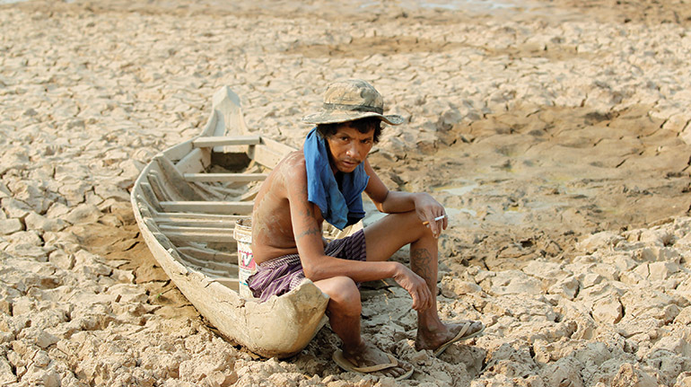 A man in Cambodia's Kandal province during a drought last year. Photo: Reuters/Pring Samrang