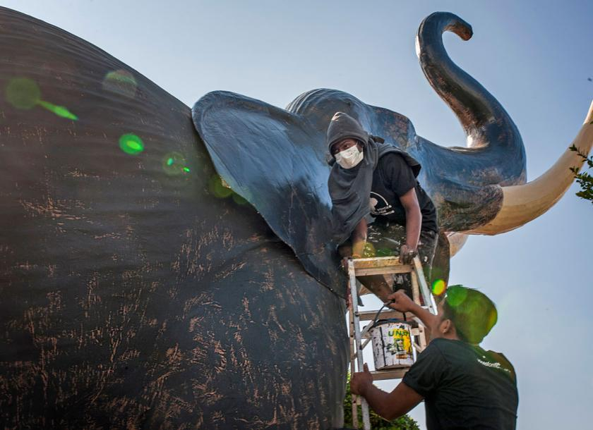 Sculptors put the finishing touches on one of seven paper mache elephant sculptures on display in exhibit 'We Love Our Momos' at Mahabandoola Park, Yangon. Nyan Zay Htet/ The Myanmar Times