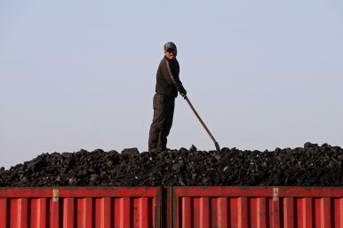 A worker speaks as he loads coal on a truck at a depot near a coal mine from the state-owned Longmay Group on the outskirts of Jixi, in Heilongjiang province, China (October 24, 2015). Image Credit: REUTERS/Jason Lee