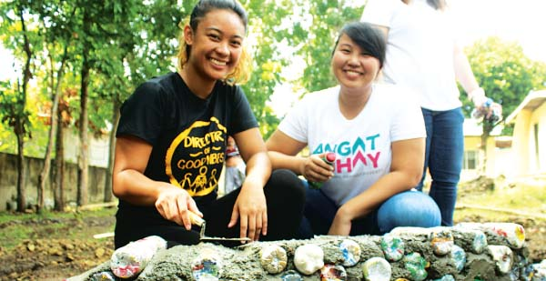 ECO-BUILDERS — The Circle Hostel's PR/Events Coordinator Jermaine Choa-Peck (left) and a volunteer from Angat Buhay build a planter box made of eco-bricks for an elementary school in Taysan, Batangas. Eco-bricks are plastic bottles stuffed with non-biodegradable wastes.