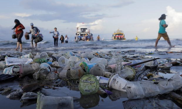 Tourists and local residents disembark a boat amid plastic rubbish in Sanur, Bali Photograph: Johannes Christo/Reuters