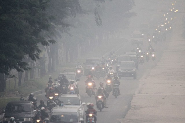 TOXIC AIR. Commuters travel along a road as thick haze blankets Pekanbaru on September 16, 2014.Forza Alfachrozie/AFP