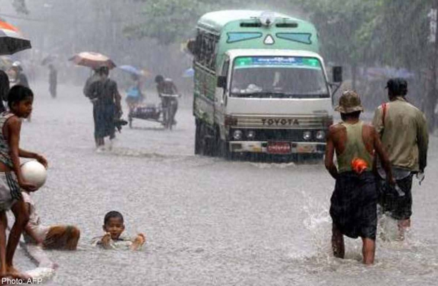 Myanmese children play along a flooded street as a vehicle make its way in Yangon