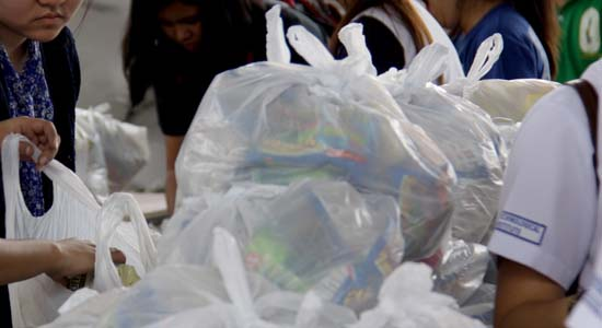 Private citizens and military personnel join hands as they volunteer to re-pack relief goods composed of food clothing and other basic necessities at the Department of Social Welfare and development headquarters in Pasay, Philippines November 18, 2013