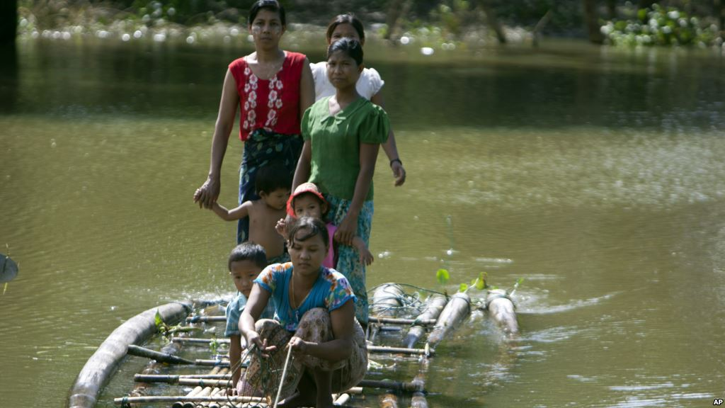 Flood victims ride a bamboo raft over a flooded road to receive relief items from private donors in Thabaung township, Ayeyarwaddy delta, Myanmar, Aug. 29, 2015.