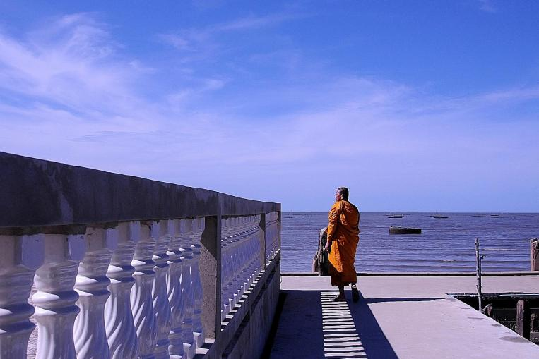 Phra Somnuek Athipanyo, the abbot of Wat Khun Samut, a Buddhist temple on the coast of the Gulf of Thailand some 30km south of Bangkok, patrols the parapet inspecting his temple's defenses against the sea. ST PHOTO: NIRMAL GHOSH