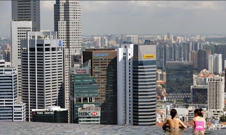 Guests of the Marina Bay Sands hotel in Singapore look over the city-state's financial district from a rooftop swimming pool. (Photo: AFP/Roslan Rahman)
