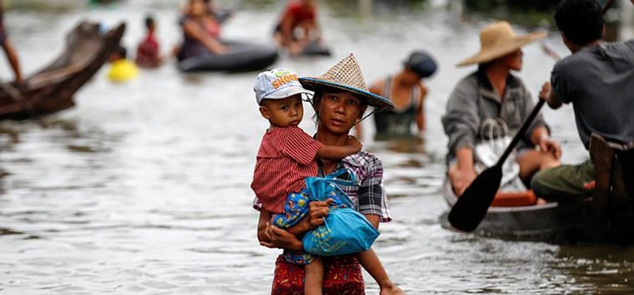 A woman carries her child as she walks through a flooded road in Kyaung Kone in Irrawaddy Region, Myanmar, August 12, 2016. / Soe Zayar Tun / Reuters