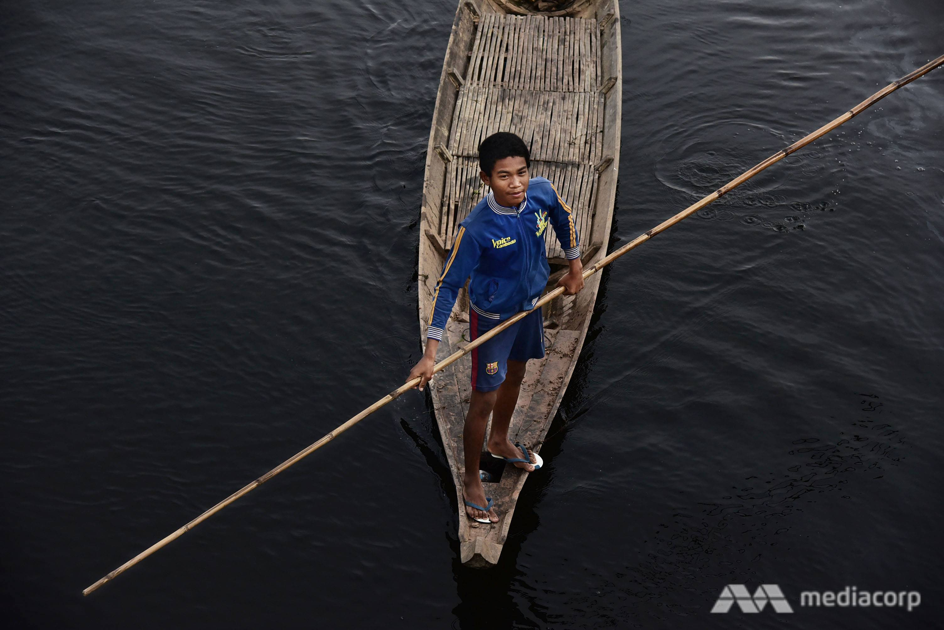 A boy rows his boat on submerged land, heading towards a floating rice field. Many farmers in Kampong Thom province still grow rice in deep water during flooding season, when water from Tonle Sap River inundates a vast area of land. (Photo: Pichayada Promchertchoo)
