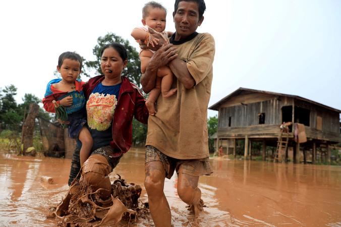 Parents evacuate with their children during a flood caused by the collapse of the Xepian-Xe Nam Noy hydropower dam in Attapeu province, Laos, on July 26, 2018. PHOTOGRAPH BY SOE ZEYA TUN, REUTERS