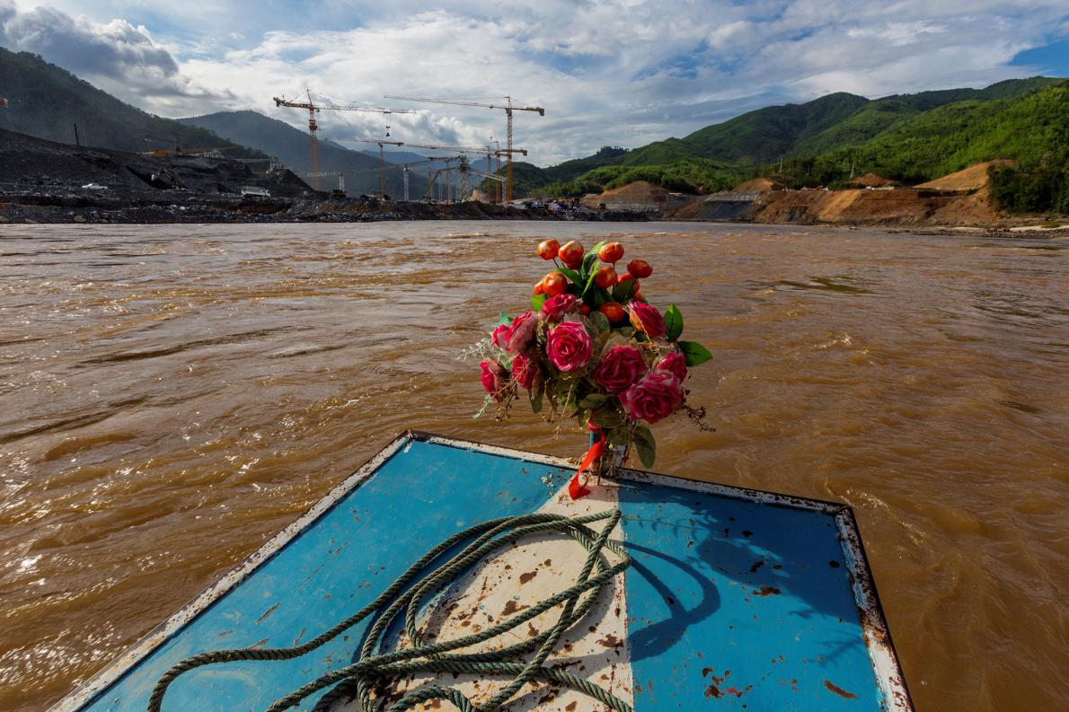 A boat adorned with artificial flowers heads toward the Xayaburi dam construction site.     PHOTOGRAPH BY DAVID GUTTENFELDER, AP/NATIONAL GEOGRAPHIC CREATIVE