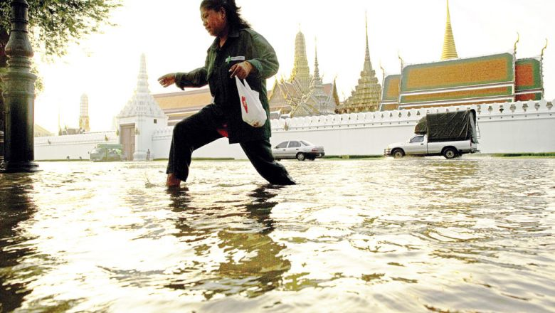 A woman walks through floodwaters in front of the Grand Palace near the Chao Praya river in Bangkok on October 28, 2011. AFP