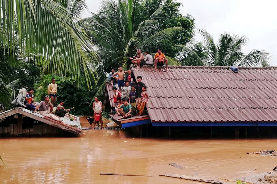 People took shelter on rooftops in Attapeu Province in southern Laos, a day after a hydropower dam's failure flooded villages and farmland. The prime minister said Wednesday that 131 people were still missing.Credit: Reuters