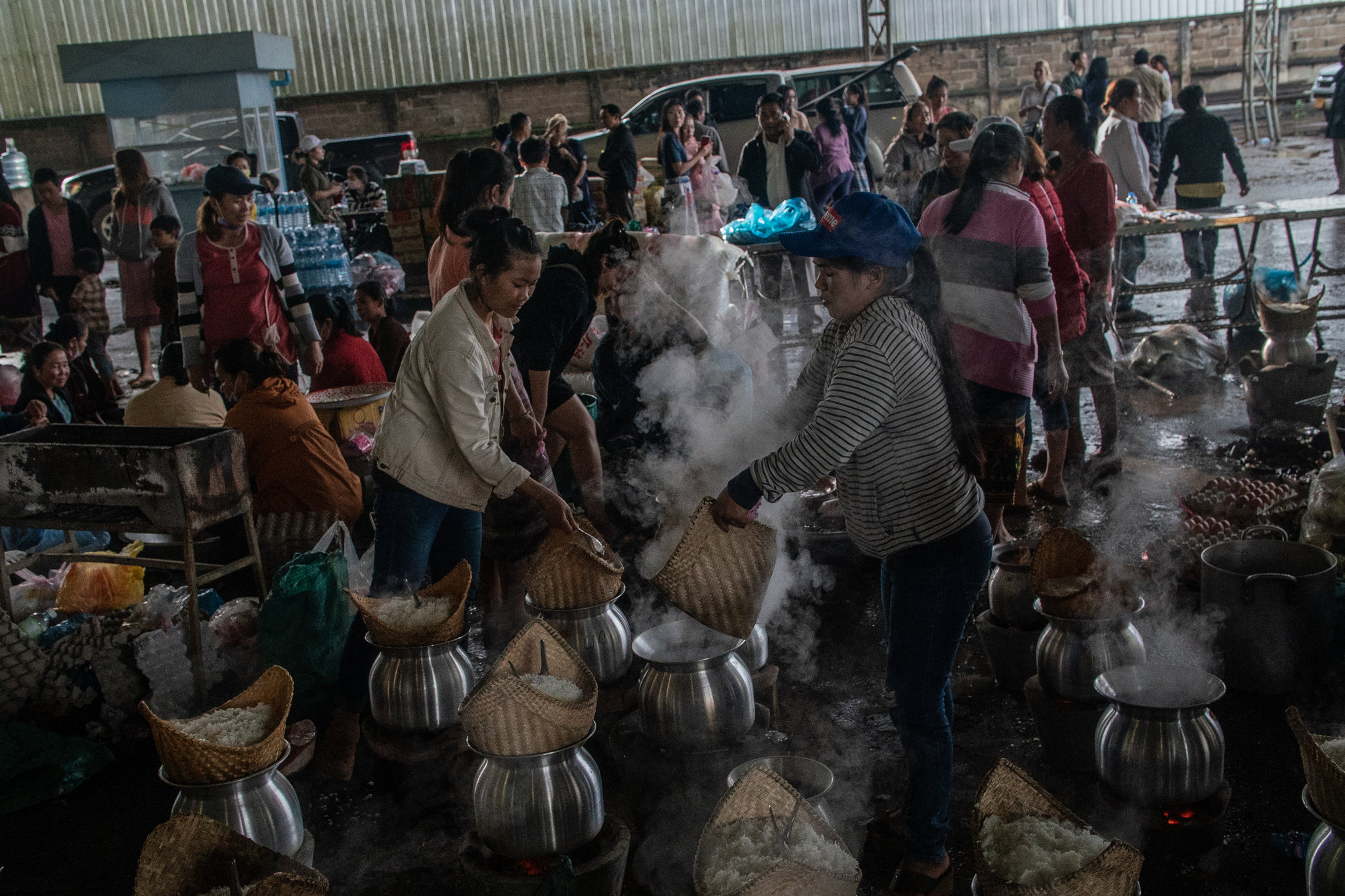 Volunteers preparing rice for people displaced by the dam collapse.CreditBen C. Solomon/The New York Times