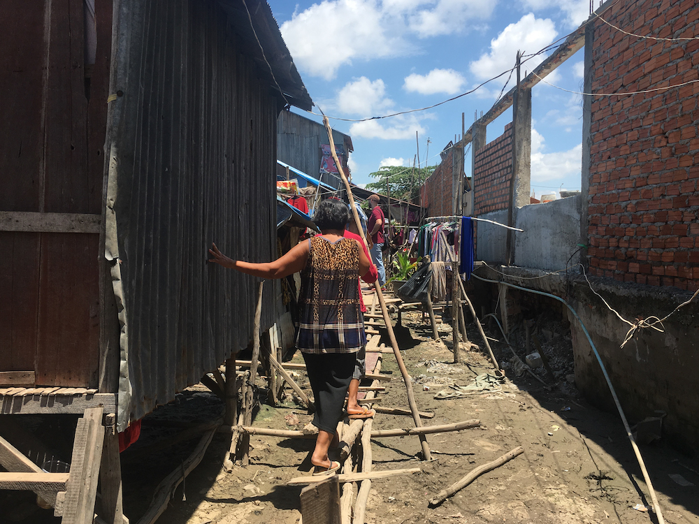 A woman walks on a makeshift bridge of wooden planks and poles in an informal settlement at the edge of Boeung Tompoun in Phnom Penh May 27, 2019. — Thomson Reuters Foundation/Rina Chandran pic