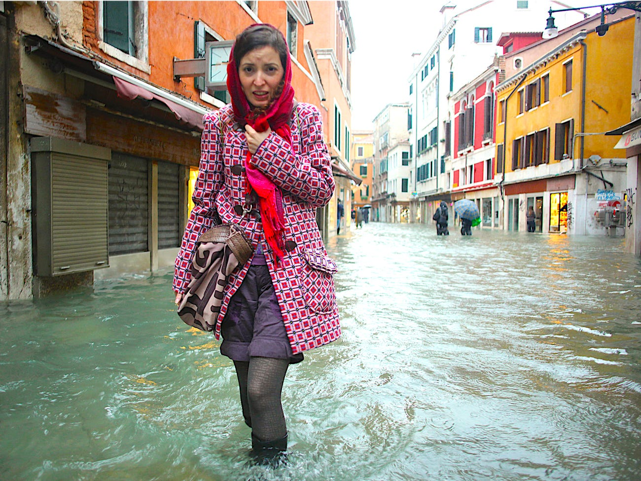 A woman walks in a flooded street during a period of seasonal high water in Venice, Italy, November 11, 2012. The water level in the canal city rose to 149 cm (59 inches) above normal. REUTERS/Manuel Silvestri