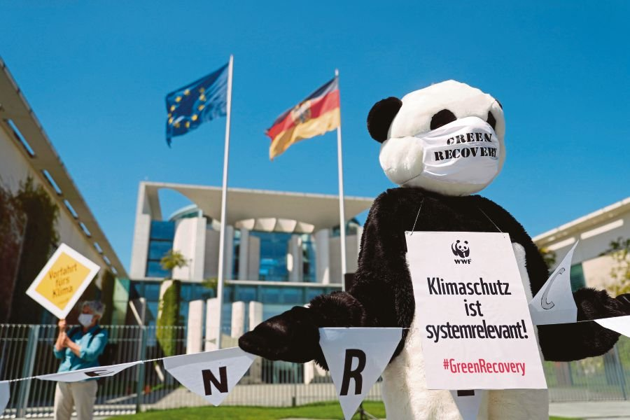 An activist dressed as a panda bear, wearing a poster reading 'Climate protection is system relevant', during a protest against the German government's rescue plans for the car industry, in front of the Chancellery in Berlin on Tuesday. -AFP pic
