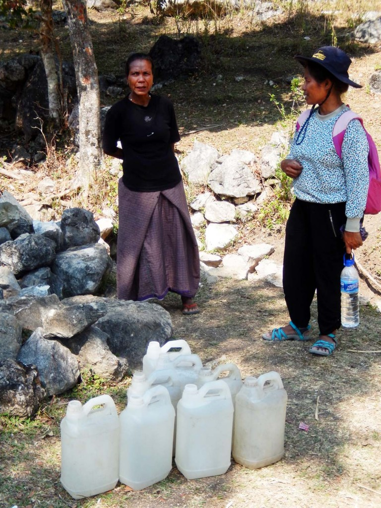 Leopoldina Guterres (right) talks with a local villager at a fresh-water spring on a mountain in Baguia, where women gather every day to fill their jugs. Scientists say climate change could exacerbate dry-season water shortages in the mountains across Timor Leste.